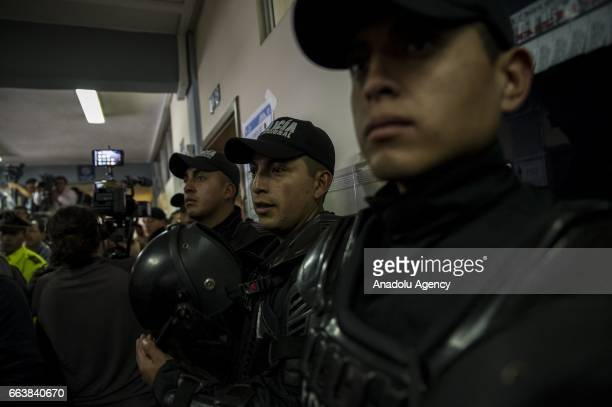 Policemen stand guard as the Ecuadorean presidential candidate of the Alianza PAIS party Lenin Moreno casts his vote at the UTE Equinoctial...