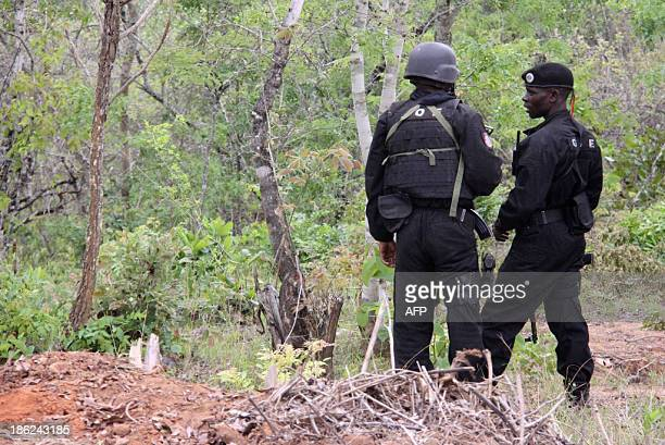 Policemen stand guard as they escort commercial vehicles traveling from Muxungue in Sofala province on October 29 2013 Mozambique troops have seized...