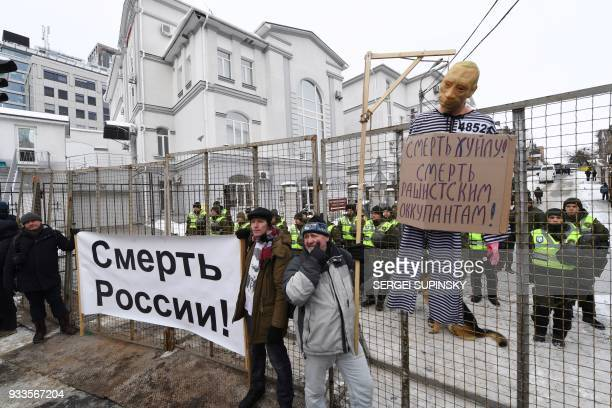 Policemen stand guard behind a fence as a mannequin depicting Russian President Vladimir Putin is hung on a gallow with a sign reading Death to Putin...