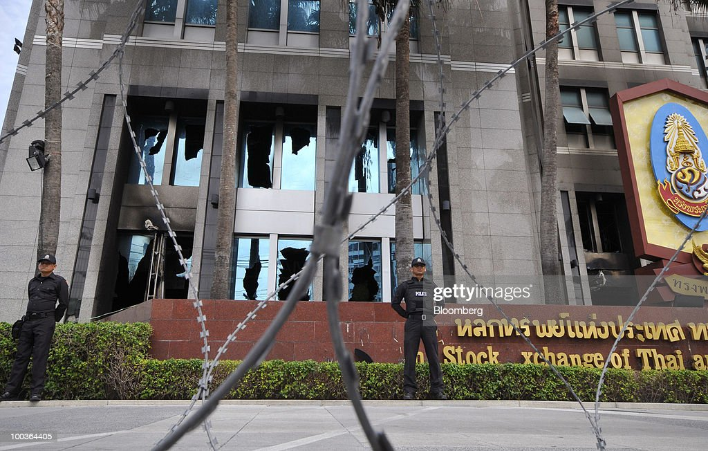Policemen stand guard behind barbed wire, in front of the broken windows of the Stock Exchange of Thailand (SET), in Bangkok, Thailand, on Monday, May 24, 2010. The Stock Exchange of Thailand returned to normal trading hours of between 10 a.m. and 4:30 p.m. today after cutting short trading hours between May 17 and 19 and shutting the market on May 20 and 21 on political unrest. Photographer: Udo Weitz/Bloomberg via Getty Images