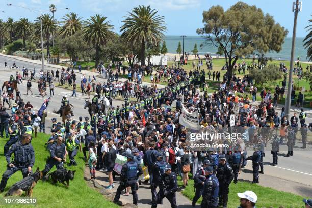 Policemen stand guard between the farright and promigrant protesters groups with opposing views during their rallies in Melbourne Australia on...