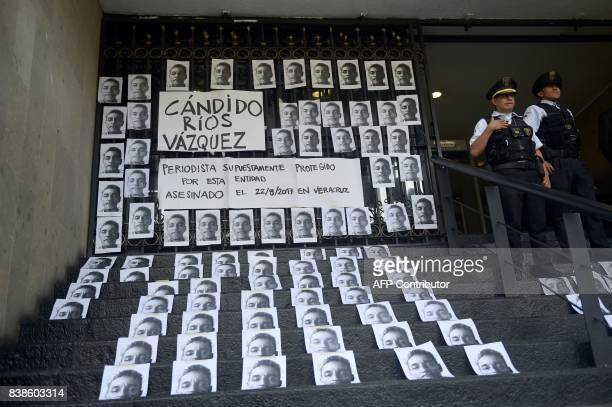 Policemen stand guard during a demonstation by journalists to demand justice por slain Mexican colleague Candido Rios at the headquarters of the...