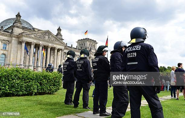Policemen stand guard during a demonstration for the rights of immigrants and refugees in front of the Reichtsag building housing the Bundestag near...