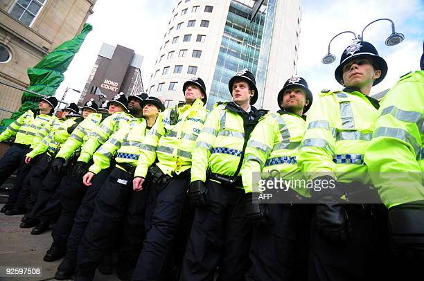 Policemen stand guard during a demonstration of supporters from the English Defence League in the city centre of Leeds on October 31 2009 The EDL...