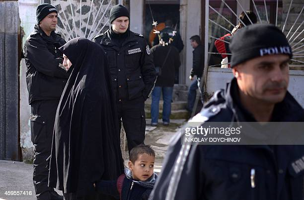 Policemen stand guard during a search operation of a house in the Roma suburb in the city of Pazardjik South West Bulgaria on November 25 2014 A...