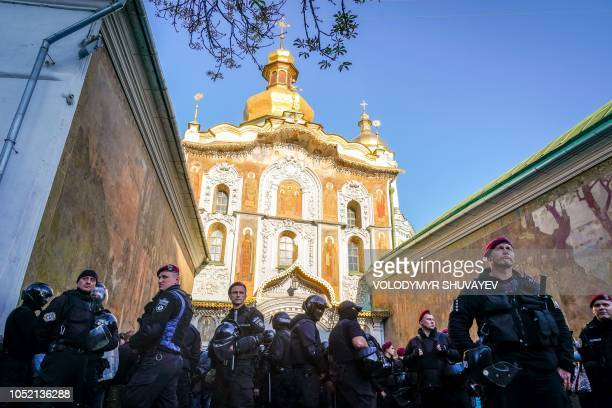 TOPSHOT Policemen stand guard in front of the central entrance of the KievPechersk Lavra monastery which is the headquarter of Ukrainian Orthodox...