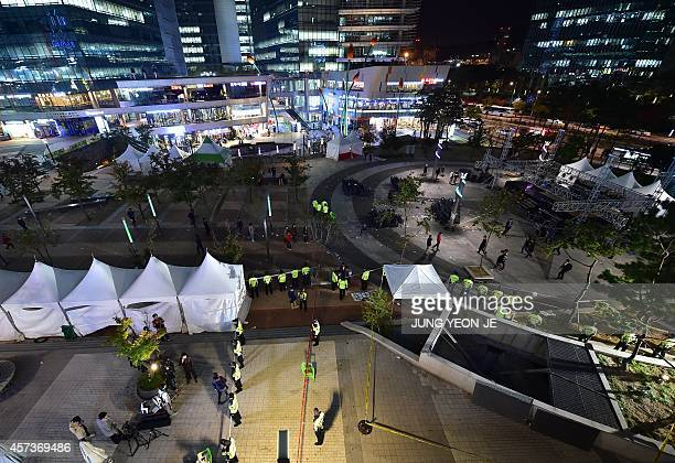Policemen stand guard near a broken ventilation grate after concert goers fell through it into an underground parking area below in Seongnam City...