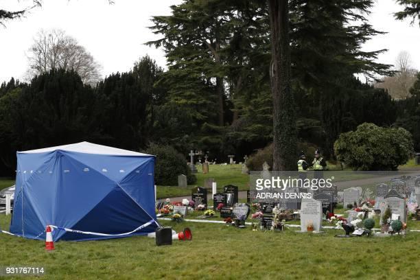 Policemen stand guard near a forensics tent in place at the London Road Cemetery in Salisbury southern England on March 14 where the wife and son of...