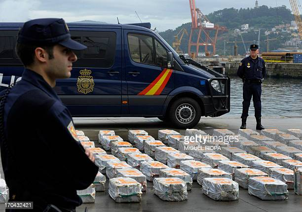 Policemen stand guard next to a part of seized drug packs on the vessel riptideat the port of Vigo northwestern Spain on June 13 Spanish police...