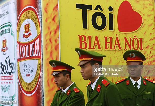 Policemen stand guard next to a poster reading 'I love beer Hanoi' during a local annual beer festival in Hanoi on December 7 2014 Thousands of local...