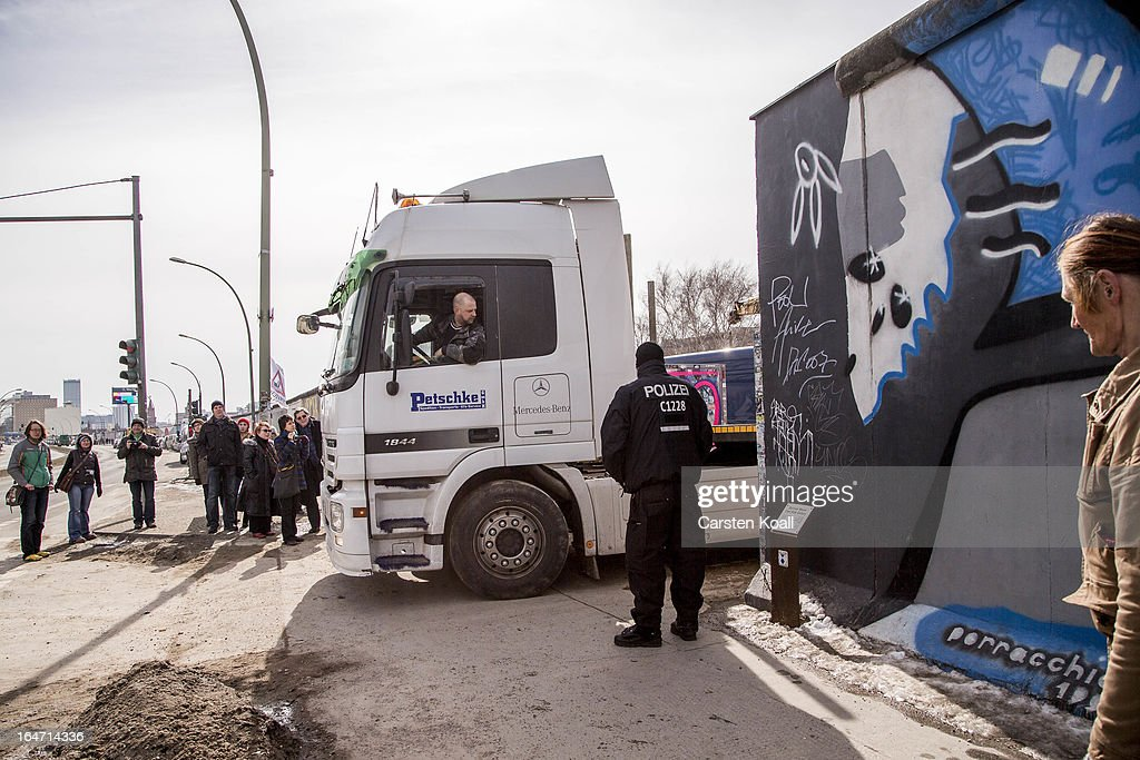 Policemen stand guard next to a section of the Berlin Wall which has been removed to make way for a luxury apartments development on March 27, 2013 in Berlin, Germany. Activists are seeking to stop a stretch of the Berlin Wall, known as the East Side Gallery, from being developed on by a real estate development company. A previous attempt by the developer to remove approximately 25 meters of the wall sparked protests that led to minor clashes with police. Negotiations had been underway and city officials had even offered the developer an alternative property, though removal continued today unannounced and to the surprise of opponents. The East Side Gallery is over one kilometer long and is among the city's biggest tourist attractions.