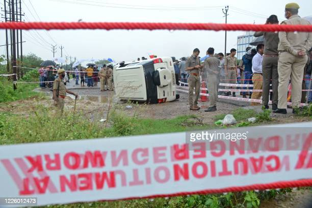 Policemen stand guard next to an overturned vehicle after the gangster Vikas Dubey was shot dead by police, on a highway at Sachendi in Uttar Pradesh...
