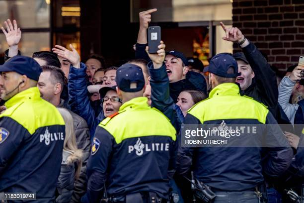 Policemen stand guard next to pro Zwarte Piet protesters during the arrival of Sinterklaas, a traditionally annual event in the Netherlands, in...
