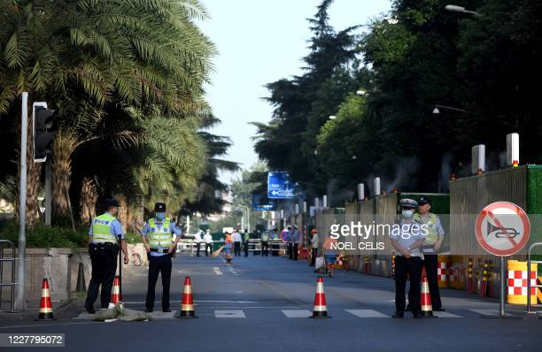 Policemen stand guard on a road leading to the US Consulate in Chengdu, southwestern China's Sichuan province on July 27, 2020. - The American flag...