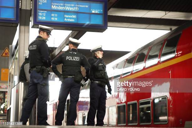 Policemen stand guard on a train station in Duesseldorf western Germany close to the Dutch border on March 18 following a shooting in the nearby...