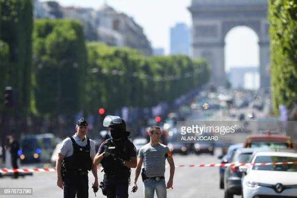 Policemen stand guard on June 19 2017 on the ChampsElysees avenue in Paris after a car crashed into a police van before bursting into flames with the...
