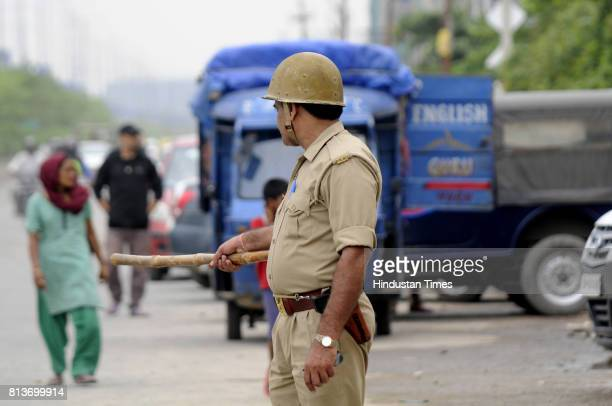 Policemen stand guard outside a housing society Mahagun Moderne in Noida Sector after locals attacked the housing colony alleging mistreatment of a...