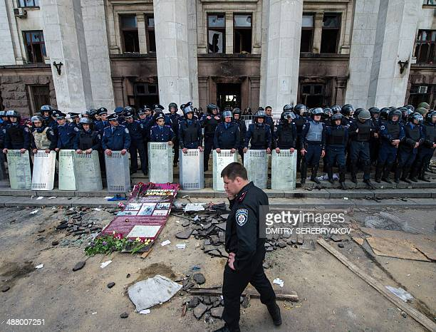 Policemen stand guard outside the charred trade union building in the southern Ukrainian city of Odessa on May 3 2014 Flowers candles and photos of...