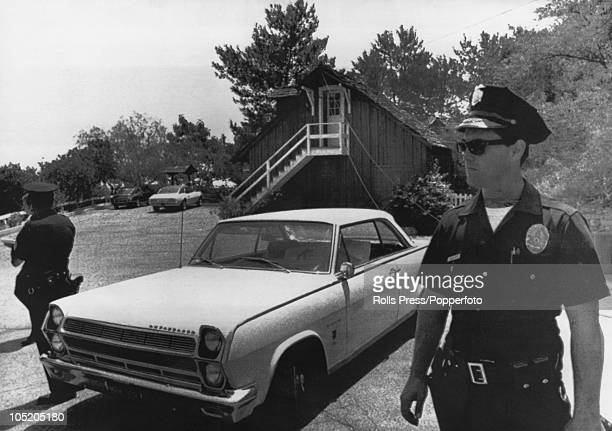 Policemen stand guard outside the home of film director Roman Polanski in west Los Angeles following the murder of his wife Sharon Tate and four...