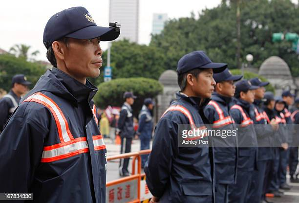 Policemen stand guard with recording devices in front of the Presidential Hall as thousands of workers gather to protest against President Ma...