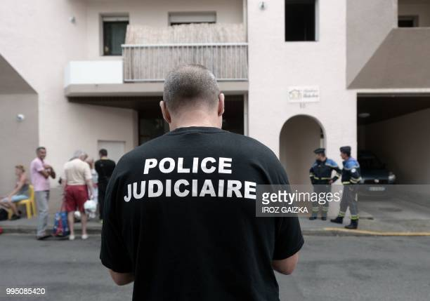 Policemen stand in front of a building after five people including one child were killed when a fire tore through an apartment in Pau southwestern...