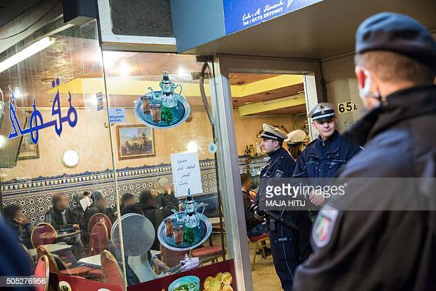 Policemen stand in front of a cafe in the socalled Maghrebdistrict of Duesseldorf western Germany during a raid on January 16 2016 Around 300...