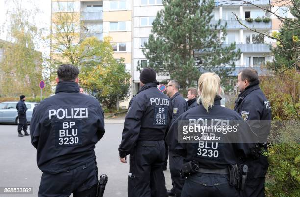 Policemen stand in front of a house at the Neu Zippendorf district in Schwerin northeastern Germany where a 19yearold Syrian man suspected of...