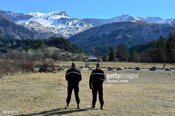Policemen stand in front of a memorial stone for the victims of the Germanwings Airbus flight near to the crash site on March 28 2015 in Le Vernet...