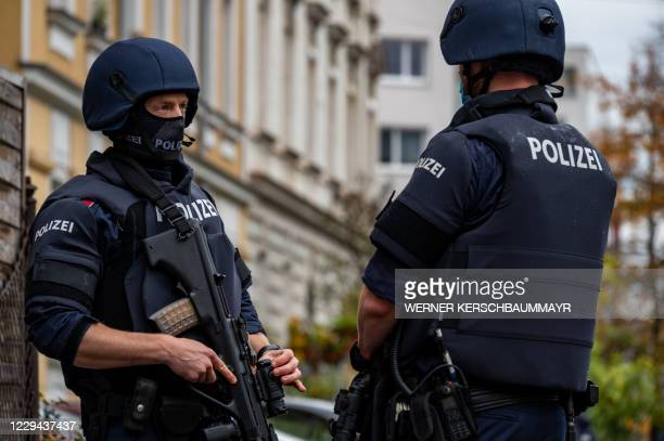 Policemen stand in front of a residential building in Linz, Austria, where a man was detained on November 3, 2020 in connection with the Vienna...