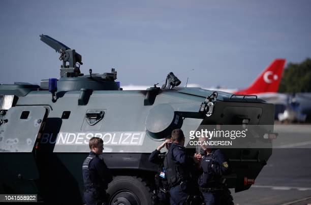 Policemen stand in front of an armored vehicle on September 27 2018 at Tegel airport in Berlin where security measures are implemented prior to a...