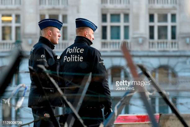 Policemen stand in front of the courthouse in Brussels on March 7 as the verdict is expected in the trial of the alleged Brussels museum attacker...