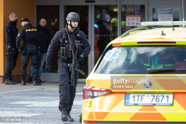 Policemen stand in front of the Faculty Hospital in Ostrava, eastern Czech Republic, after a gunman opened fire killing six people, on December 10,...