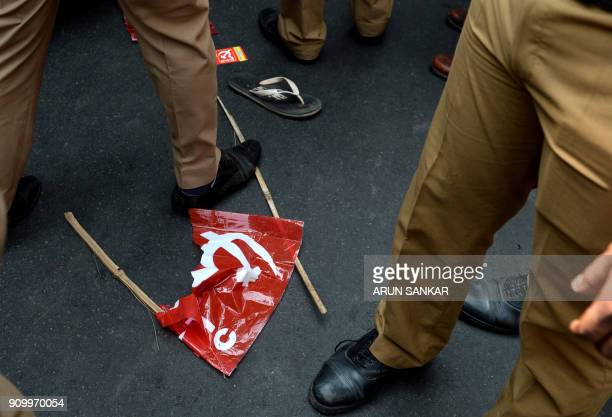 TOPSHOT Policemen stand near a damaged communist flag as members of Communist Party of India along with Trade Unions demonstrate during a national...