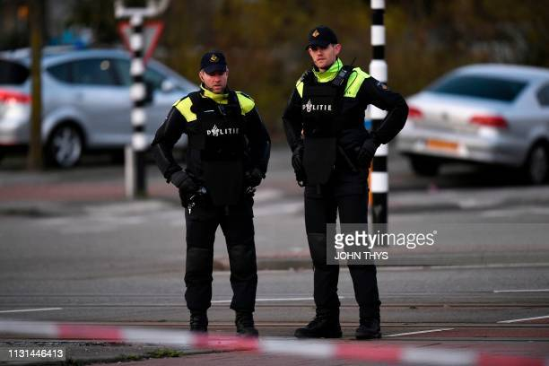 Policemen stand near a tram where a gunman opened fire killing at least three persons and wounding several in what officials said was a possible...
