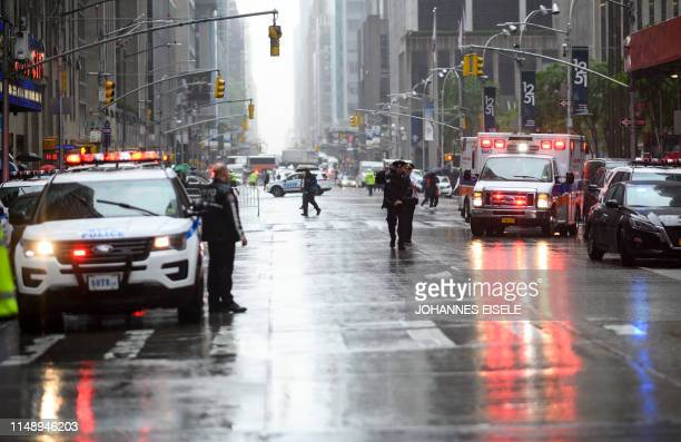 Policemen stand near emergency services vehicles after a helicopter crashlanded on top of a building in midtown Manhattan in New York on June 10 2019...