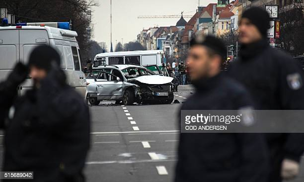 Policemen stand near the wreckage of a car after a blast caused by an explosive device killed its driver travelling down a street in central Berlin...