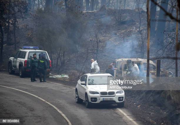 Policemen stand next a van where two people were trapped by flames of a fire in their vehicle in Chandebrito near the town of Nigran northwestern...
