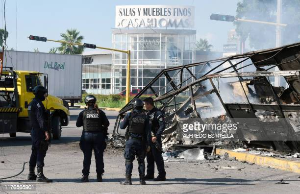 Policemen stand next to a burnt vehicle after heavily armed gunmen waged an allout battle against Mexican security forces in Culiacan Sinaloa state...
