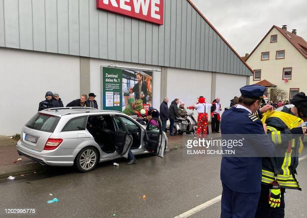 Policemen stand next to a car in front of a supermarket in Volkmarsen near Kassel central Germany on Rose Monday February 24 2020 Several people were...