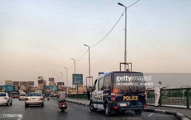 Policemen stand next to a patrol car parked along the 6th of October bridge crossing the Nile in the centre of the Egyptian capital Cairo on...
