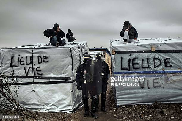 TOPSHOT Policemen stand next to migrants on shelters roof as agents dismantle shacks on March 1 2016 in the 'Jungle' migrant camp in the French...