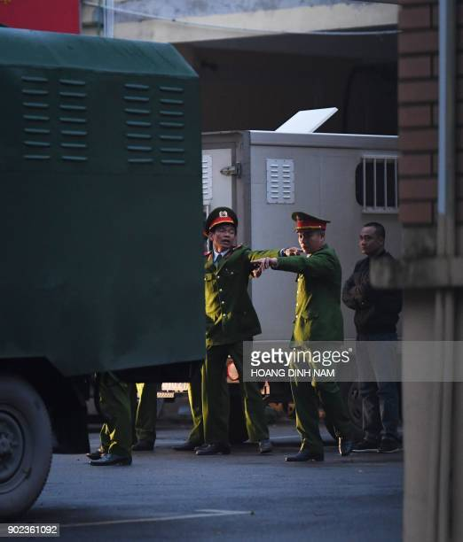 Policemen stand next to police trucks transporting defendants at the courtyard of the Hanoi People's Courthouse prior to the beginning of the trial...