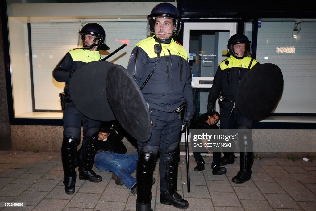 Policemen stand next to protests that erupted around the Turkish consulate after Dutch authorities barred Turkish ministers from visiting, early March 12, 2017 in Rotterdam in the Netherlands. After initially dispersing, the crowd began to gather in smaller groups again, with the police once again moving in, an AFP correspondent said. The move came as the city's authorities expelled Turkey's Family Minister Fatma Betul Sayan Kaya and escorted her back to the German border. PHOTO / ANP / Bas Czerwinski / Netherlands OUT
