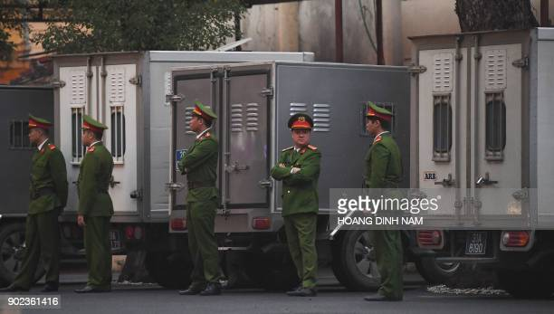 Policemen stand next to trucks transporting defendants at the courtyard of Hanoi People's Courthouse prior to the beginning of the trial of Trinh...