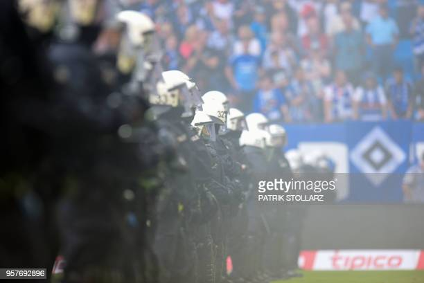Policemen stand on the pitch after Hamburg supporters throw fireworks during the German first division Bundesliga football match Hamburger SV vs...