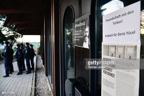 Policemen stand outside the Festhalle Bad Rotenfels hall while a plakat for the arrested journalist Deniz Yuecel stick at the entrance door after a...