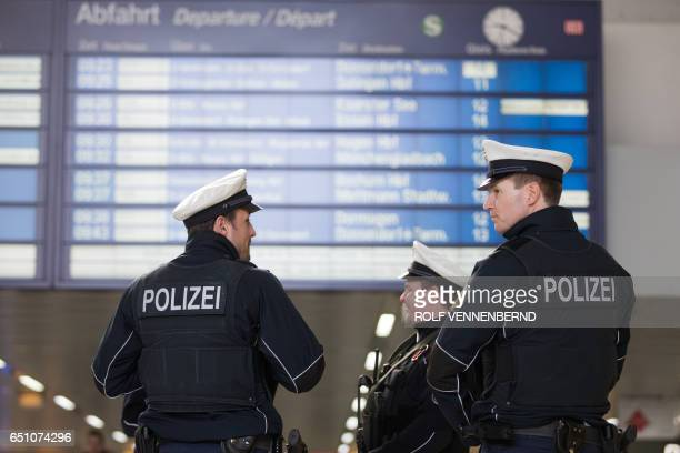 Policemen stand under a schedule board on March 10 2017 in Duesseldorf western Germany one day after German police have arrested an axewielding...