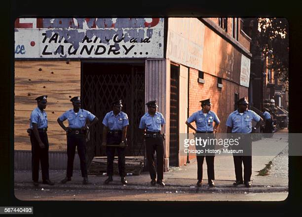 Policemen standing outside a graffited building during unrest following the Watts Riots in Los Angeles California Chicago Illinois August 1965