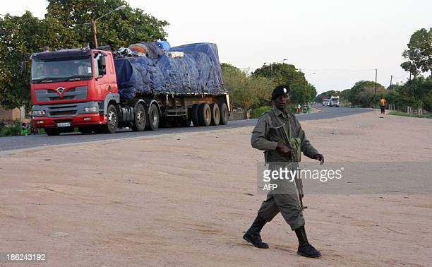 Policemen stands guard as police escorted commercial vehicles traveling from Muxungue in Sofala province on October 29, 2013. Mozambique troops have...