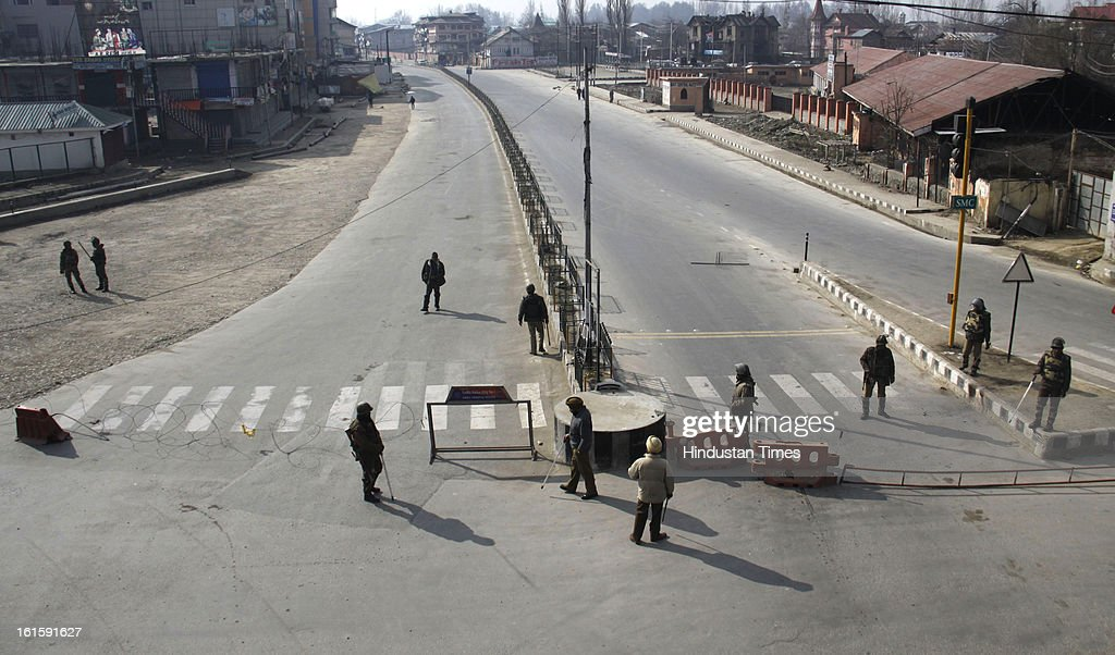 Policemen stands near a barricade on the 4th day of curfew, on February 12, 2013 in Srinagar, India. Curfew imposed in Srinagar after Afzal Guru's execution.